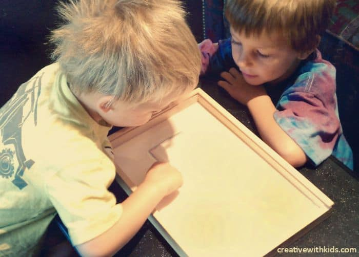 Helping brother write in sensory tray