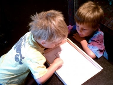 Helping write in sensory tray